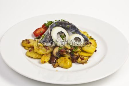 fried potatoes with herring fillet on