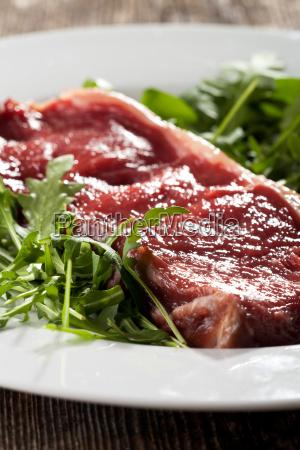 raw sirloin steak on rocket