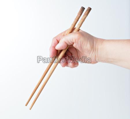 hand using chopsticks