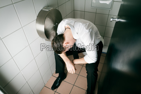 young drunk man sleeping on toilet
