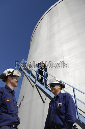 fuel storage tower with oil workers