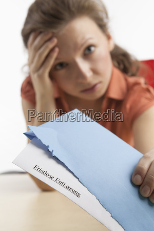 young woman with termination letter looks