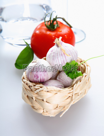 a basket with tomato and garlic