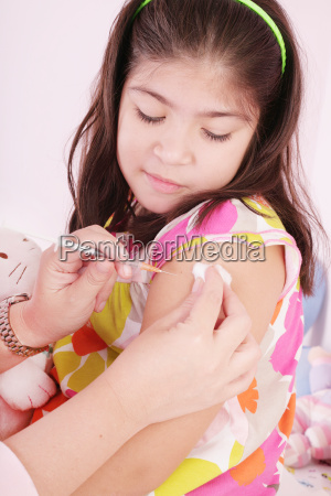 child receiving an injection by the