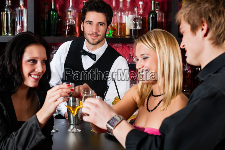 barman behind counter friends drinking at