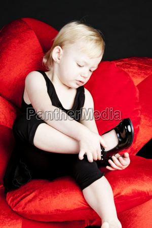 little girl with black shoes sitting