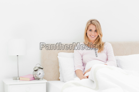 woman leaning up against the headboard