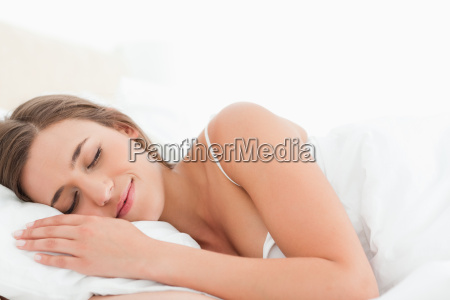 woman lying in bed asleep smiling