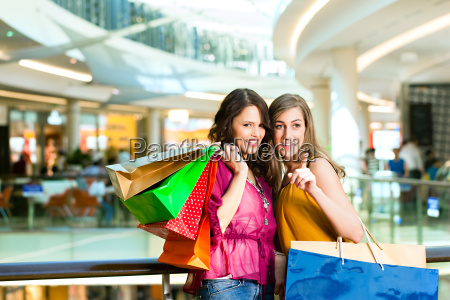 two girlfriends shopping in a mall