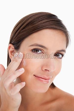 teenager applying cream on her face