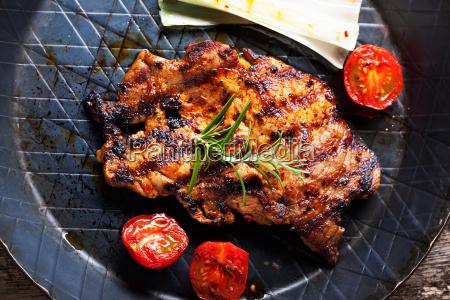 grilled pork steak in an iron