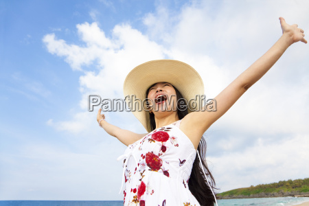 happy young woman raised hands on