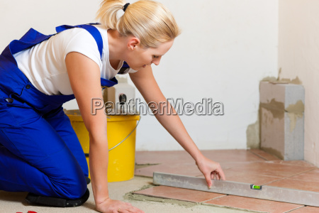 laying female tiler when tiles