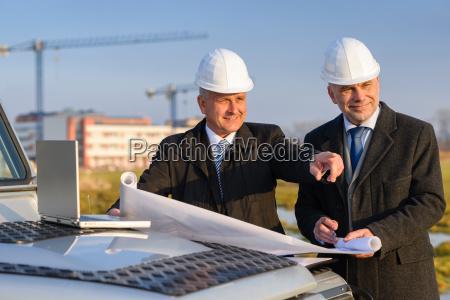 architect developer point at construction site