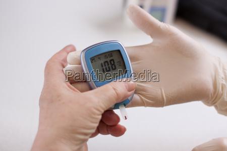 altenpflegerin measures the glucose level of