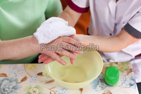 geriatric nurse washes the patients hands
