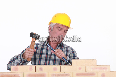 worker using hammer and chisel on