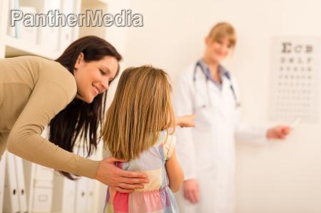 pediatrician pointing eye chart at medical