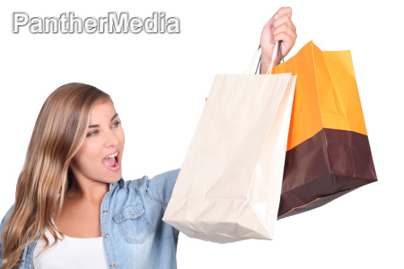 blond woman stood holding shopping bags