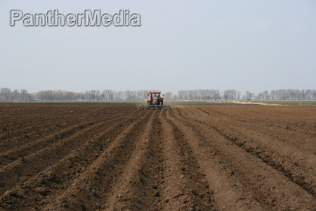 tractor plows and pulls rows on