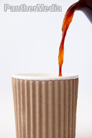 paper cup being filled with coffee