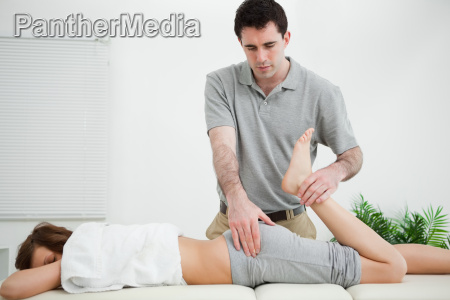 woman lying while being stretched by