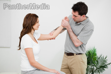 serious practitioner touching the elbow of