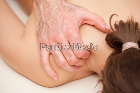 chiropractor squeezing the shoulder of woman