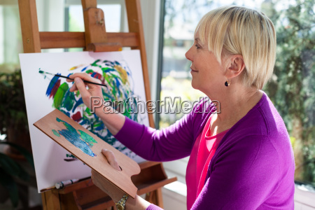 happy elderly woman painting for fun