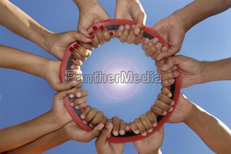 several hands holding a disc together