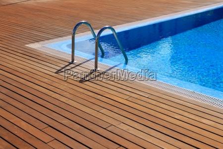 blue swimming pool with teak wood
