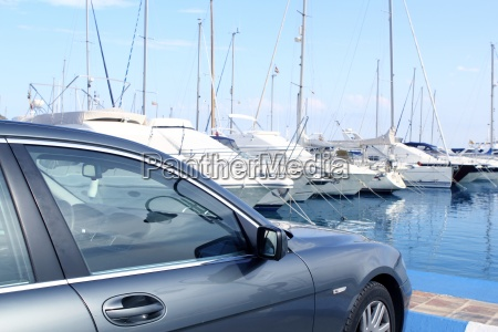 luxury car and yacht sailboats on
