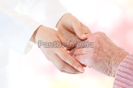 doctor holding senior ladys hand