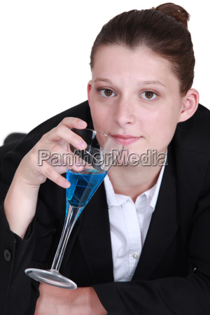 woman in a suit drinking a