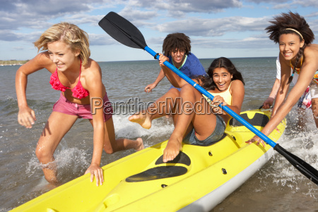 teenagers in sea with canoe