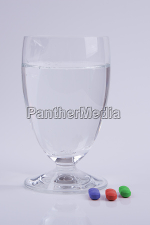 water glass with colored tablets