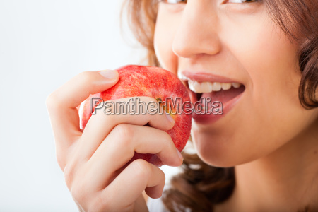 young woman is biting into an
