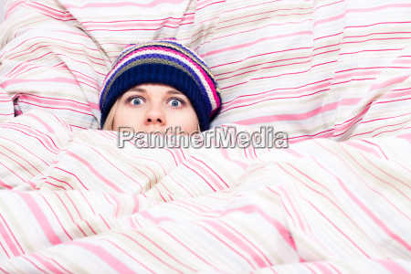 scared woman hiding in duvet