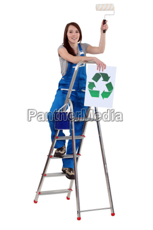 tradeswoman holding a paint roller and