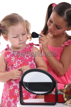 two little girls playing with make