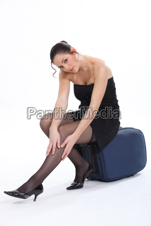 woman sitting on a suitcase smoothing