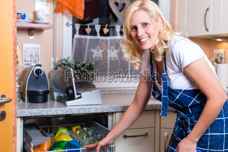 housewife wash the dishes with dishwasher