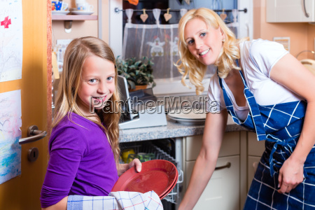 housewife with daughter washing dishes