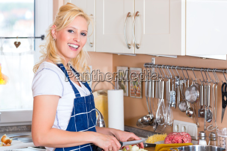 young woman is cooking and cutting