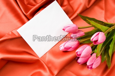 envelope and flowers on the satin