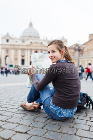 pretty young female tourist studying a