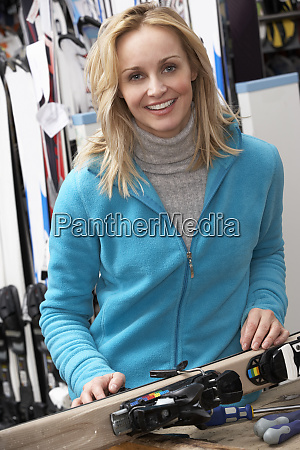 female sales assistant with skis in