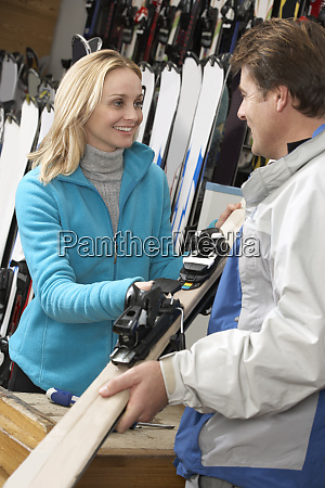 female sales assistant handing skis to