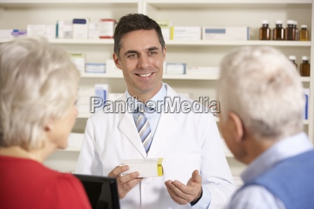 american pharmacist with senior couple in