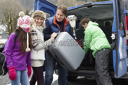 family unloading luggage from transfer van
